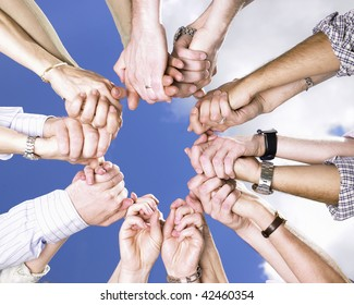 Circle of people's arms, holding hands, with blue sky and clouds in the background. Square.