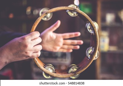 A circle -shape wooden tambourine musical percussion rattle rhythm with the both hands. (vintage style)