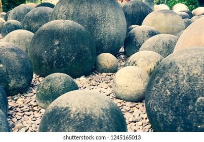 circle stone statue in Nong Nooch Tropical Botanical Garden (cross process)