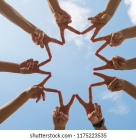 a circle of ten hands making peace signs under a blue sky with white clouds