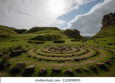 Circles made of stones on a green field surrounded by rocky cliffs of a so called Fairy Glen, the Isle of Skye, Scotland, UK