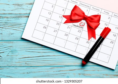 circling the date of the 15th day in the calendar. Concept of fertility chart, trying to have baby, Reminder Ovulation in graph, Planning of pregnancy. Red bow. On a blue wooden background.