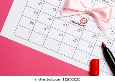 circling the date of the 15th day in the calendar. Concept of fertility chart, trying to have baby, Reminder Ovulation in graph, Planning of pregnancy. Pink bow. on a pink background.