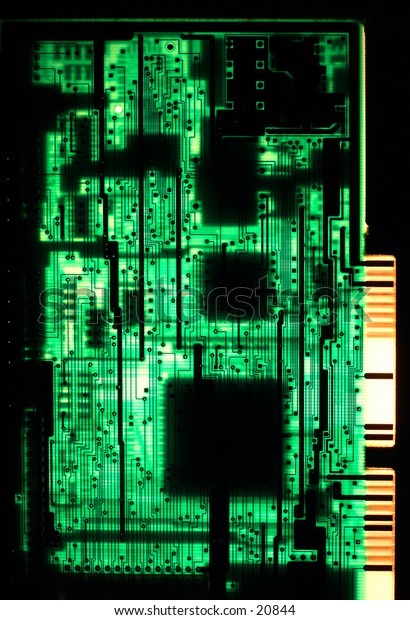 A circuit board from a late 1980s 286 computer, viewed from  behind and backlit.