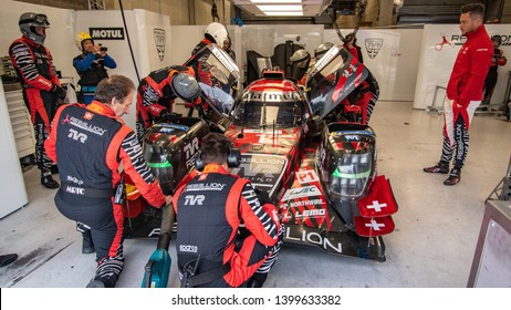 Circuit de Spa-Francorchamps, Belgium, 3 May 2019. Friday practice WEC Total 6 Hours of Spa. Pilot André Lotterer (right) watches Rebellion Racing LMP1 undergoing maintenance in the garage.