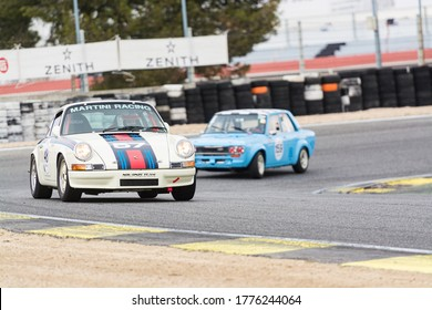 Circuit of Jarama, Madrid, Spain; April 03 2016: Porsche 911 2.4 being chased by a Datsun 1200 in a classic cars race