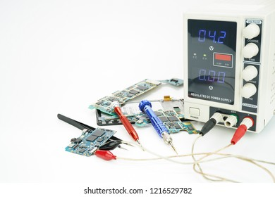 Circuits board of cellphone measuring the voltage with DC Power Supply on white background.Analysis to repair.Selective focus.