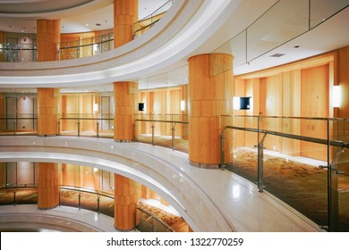 The circular atrium of hotel features a sightseeing elevator, warm lighting and sense of design with glass balustrade and woodiness metope adornment.