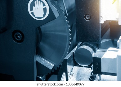 The  circular blade saw machine cutting raw metals rods .The industrial sawing machine cutting the material rod.