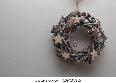 Circular Branches Woven: Christmas Decoration with Wooden Star and Little Pine Cones.
