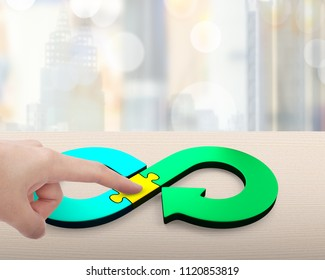 Circular economy concept. Forefingers pointing at arrow infinity recycling symbol of jigsaw puzzle pieces.
