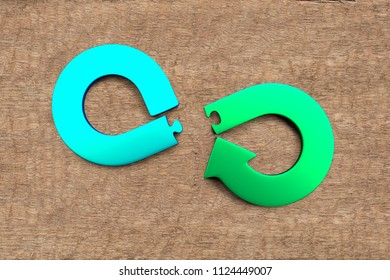 Circular economy concept. Green and blue arrow infinity recycling symbol of puzzle pieces separated, on wooden texture background.