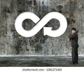 Circular economy concept. Thinking businessman in front of white arrow infinity recycling symbol hole on old dirty concrete wall.