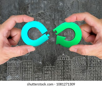 Circular economy concept. Two hands assembling arrow infinity recycling symbol of jigsaw puzzle pieces, on city buildings doodles background.