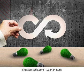 Circular economy and green energy concept. Man's hand holding metal arrow infinity recycling symbol, with green grass of light bulbs on the table.