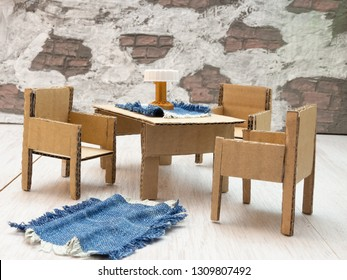 Circular economy, reused cardboard furniture. Dollhouse with chairs and tables from cardboard. A floor rug and tablecloth of reused jeans.