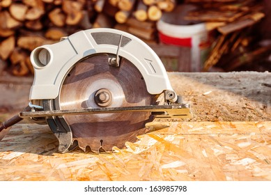 Circular electric saw on the desktop with the wood.