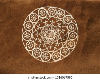 A circular floral design or Madala painted on mud wall covered with cow dung. An Indian tribal art and drawing.