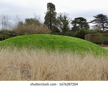 Circular grassy mound surrounded by tall white grasses in springtime in England
