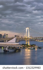 Circular highway leading to the Rainbow Bridge with Cargo and cruise ships moored or sailing in Odaiba Bay of Tokyo.