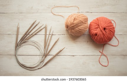 Circular knitting needles and beige, rust color wool yarn on the wooden background