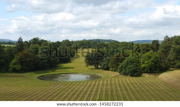 Circular pond in a grass field with trees.