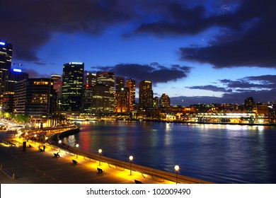 circular quay with sydney city skyline at night with clouds and lights