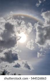 Circular rainbow with Sun and clouds sky