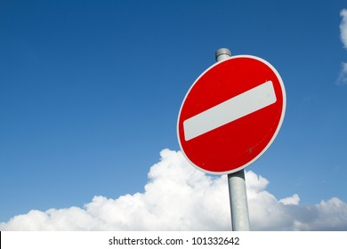 A circular red sign with a white bar indicating 'NO ENTRY' on a grey metal post against a blue cloudy sky.