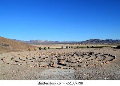 A circular rock labyrinth sits atop a hill at the town of Tecopa Hot Springs overlooking the vast desert with mountains in background.