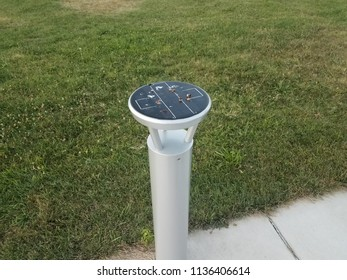 circular solar panel light with bird poop and sidewalk and green grass