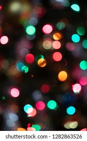 Circular spots and specs of multi-colored lights set on a dark background created from the camera's macro bokeh and off-focus to show glittering effect.