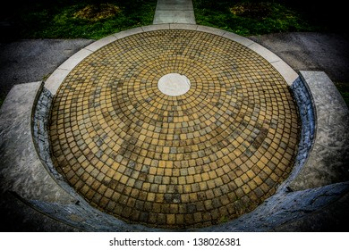 A circular stone floor with a round stone center piece surrounded by a raised stone wall and a concrete walking path