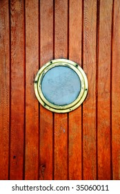 circular window on a timber door of a boat