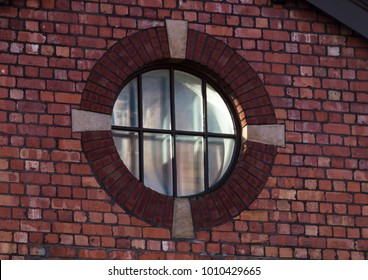 A circular window one a red brick wall