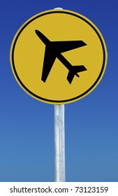 Circular yellow road sign on a blue sky background with an aeroplane on it.