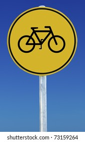 Circular yellow sign on blue sky background. Sign features a picture of a bicycle