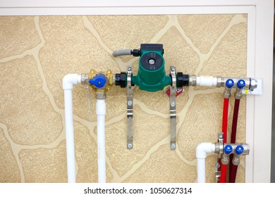 Circulation Pumps on theof pipes of a warm floor under a laminate of a parquet and a tile Floor heating pipe
