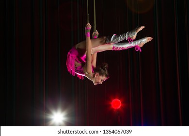 Circus artist acrobat performance. The girl performs acrobatic elements in the air. Circus gymnast on the stage