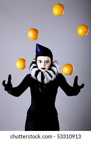 Circus fashion mime juggles with five oranges. Photo.