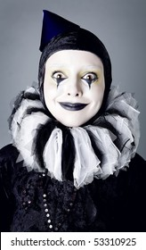 Circus fashion mime posing on a grey background. Photo.