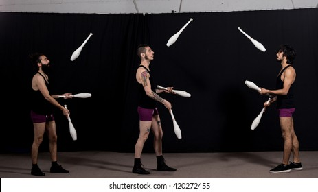 Circus jugglers during their batons show. Teamwork concept