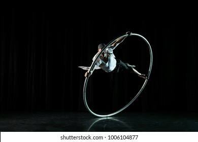 Circus performer artist in a Cyr Wheel (Roy Cyr) in theatre at a black background
