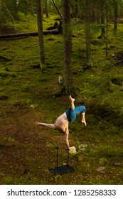 Circus performer doing one arm handstand in a forest