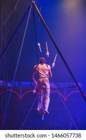 Circus performer juggling on slackwire