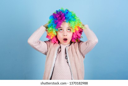 Circus school concept. Acting school for children. Develop acting talent into career. Girl artistic kid practicing acting skills. Kid colorful curly wig artificial hair clown style blue background.
