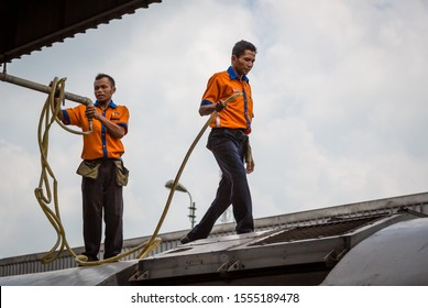 "Cirebon, Indonesia - 4 February 2015: Two men of the railway staff on the wagon roof are about to refill the water tanks of the Diesel Train CC 2061331""DIPO INDUK YK"" at Cirebon Railway Station"