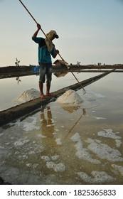 Cirebon, Indonesia - march, 2020: People working in salt pond in Cirebon, Indonesia.