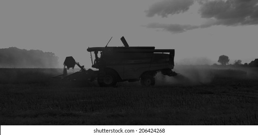 Cirencester, Gloucestershire, July 17th 2014 - Massey Ferguson Combine Harvester working the field at night - Black and White