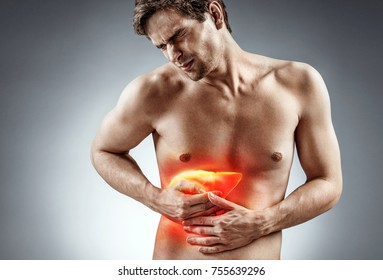 Cirrhosis of the liver. Photo of man holding his hand in area liver and grimacing in pain on grey background. Medical concept